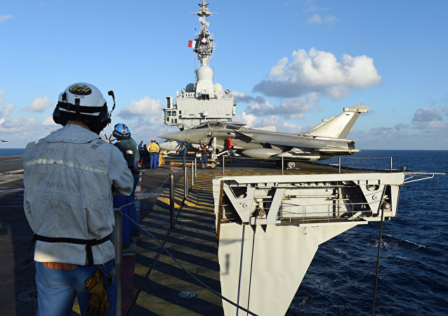 French navy technicians work near a French Rafale aircraft on the flight deck on the aircraft carrier Charles-de-Gaulle, in eastern Mediterranean sea, on November 21, 2015