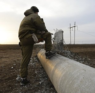 A man steps on a damaged electrical pylon near the village of Chaplynka in Kherson region, Ukraine, November 22, 2015