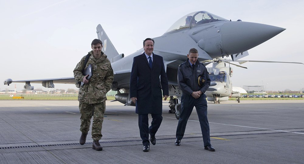 Britain's Prime Minister David Cameron (C) walks with Group Captain David Manning (R) past an RAF Eurofighter Typhoon fighter jet during his visit to Royal Air Force station RAF Northolt in London, Britain November 23, 2015