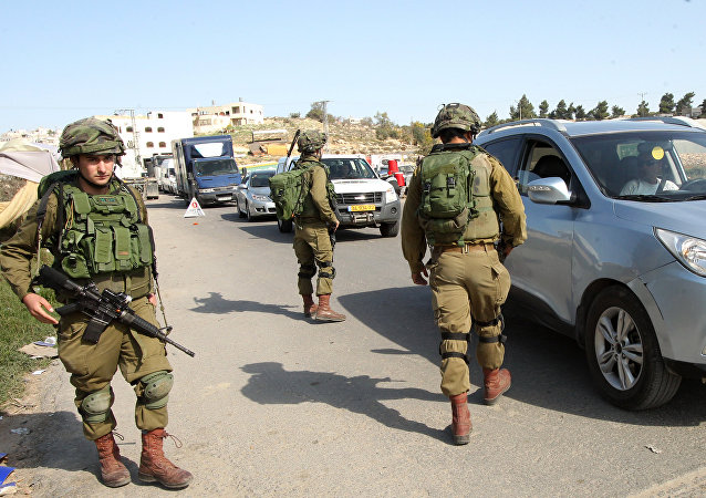 Israeli soldiers man a checkpoint at one of the entrances of the West Bank city of Hebron, on November 23, 2015