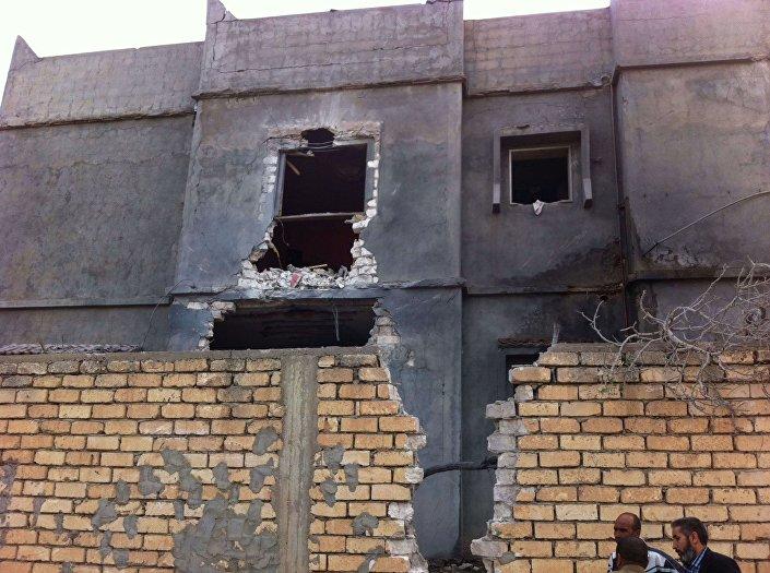 Men stand beside a damaged building near Mitiga airport in Libya's capital Tripoli
