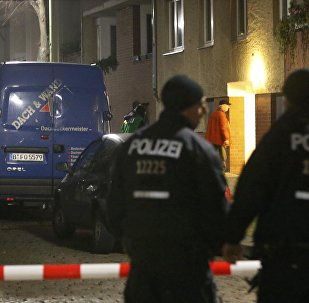 Police officers stand guard as colleagues search a suspicious vehicle during a raid on a building in Britz, south Berlin, Germany