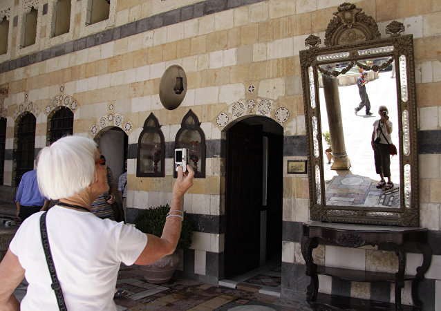 Tourist takes a photo during her visit to Al-Azem Palace that houses the museum of arts and popular traditions in the Old City of Damascus, Syria