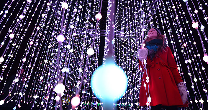 A woman poses for pictures in a light display during a photocall at Kew Gardens in south west London, on November 24, 2015, during their launch of the Christmas at Kew Gardens event