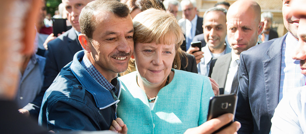 Asylum seeker (C, L) takes a selfie picture with German Chancellor Angela Merkel (C, R) following Merkel's visit at a branch of the Federal Office for Migration and Refugees and a camp for asylum-seekers in Berlin on September 10, 2015.