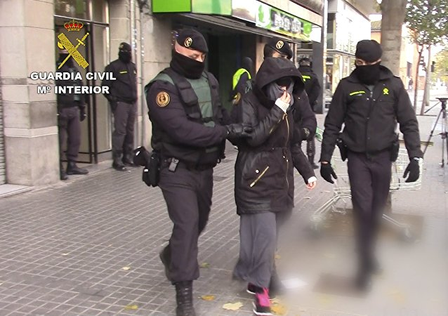 Spanish police escort a woman suspected of recruiting fighters for the Islamic State in Granollers, near Barcelona, in this handout picture from the Spanish Interior Ministry received November 28, 2015. Spain said it arrested three people on Saturday suspected of recruiting fighters for Islamic State in Syria and Iraq