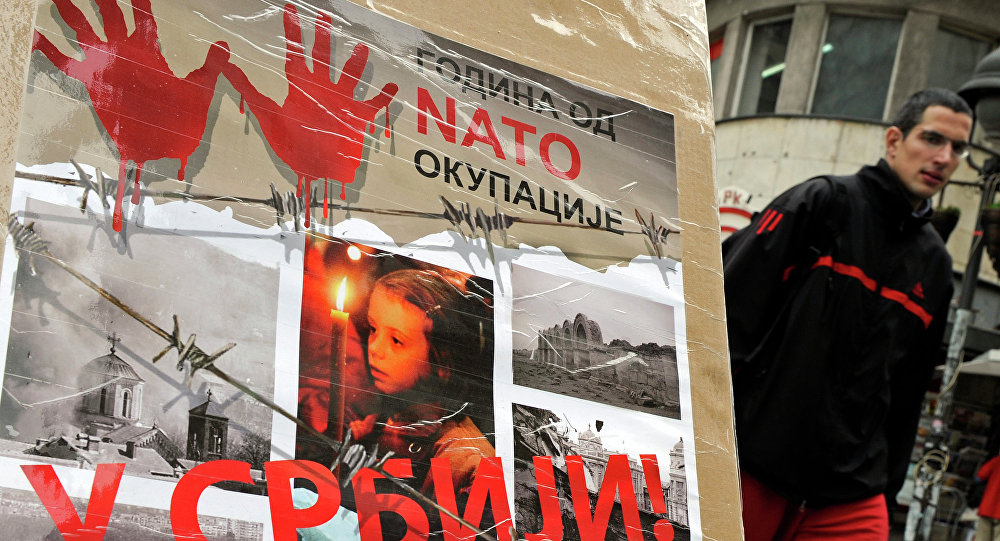 "A man walks past a poster with the reading ""Ten years of NATO occupation of Serbia"", and displaying images from 1999 NATO air campaign against Serbia and Montenegro."
