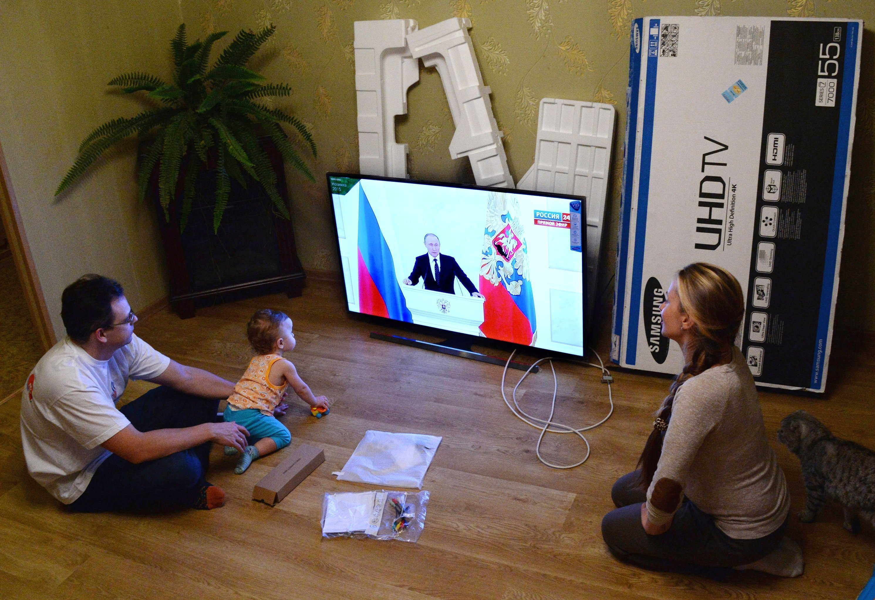 A young family in Vladivostok watches the live broadcast of Russian President Vladimir Putin's Presidential Address to the Federal Assembly