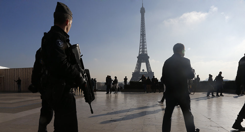 French police officers patrol near the Eiffel Tower, in Paris, Monday Nov. 23, 2015.