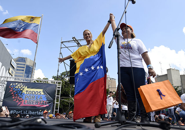 Lilian Tintori (L), wife of jailed Venezuelan opposition leader Leopoldo Lopez, holds up the hand of a supporter during a rally in Caracas