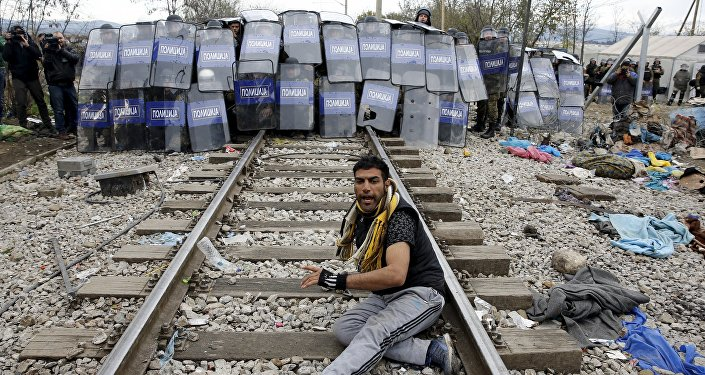 A stranded migrant reacts in front of a Macedonian police cordon as they clash after a migrant was injured when he climbed on top of a train wagon, near the village of Idomeni, Greece, November 28, 2015.