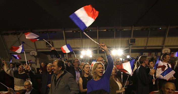 Supporters of far right National Front party regional leader for southeastern France, Marion Marechal-Le Pen, wave flags at a meeting after the results of the first round of the regional elections, in Carpentras, southern France.