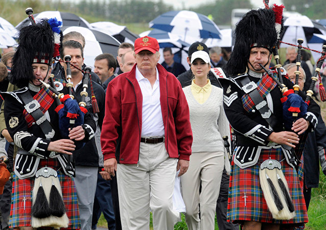 US tycoon Donald Trump (C) is escorted by Scottish pipers as he officially opens his new multi-million pound Trump International Golf Links course in Aberdeenshire, Scotland, on July 10, 2012.