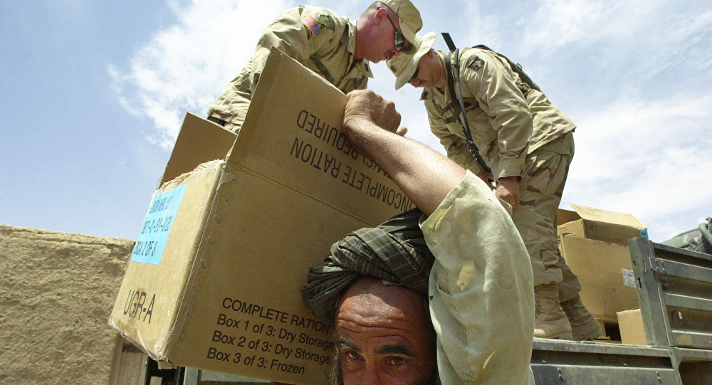A man carries a box with donated food from the 101st Airborne Division  in the village of Khoshab, Afghanistan (File)