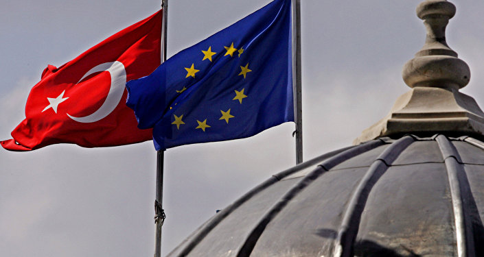 Flags of Turkey, left, and the European Union fly over the dome of a mosque in Istanbul, Turkey