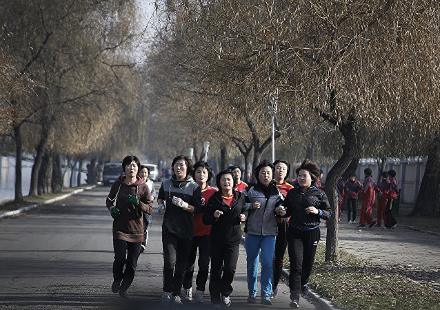 North Korean ladies jog along the Pothong River on Tuesday, Dec. 1, 2015, in Pyongyang, North Korea