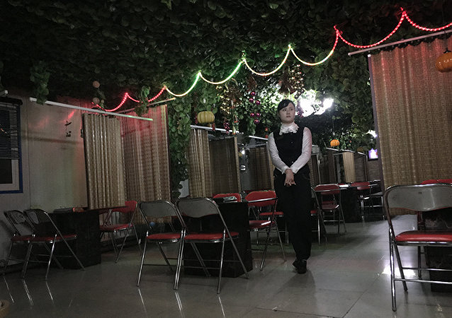 In this Monday, Nov. 30, 2015, photo, a waitress waits to serve customers in a Korean BBQ restaurant in Pyongyang, North Korea