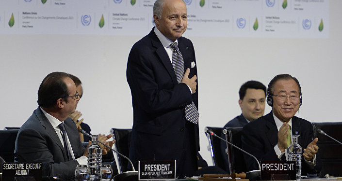 French Foreign Minister Laurent Fabius (C) is applauded by French President Francois Hollande (L) and United Nations Secretary General Ban Ki-moon (R) after a statement at the COP21 Climate Conference in Le Bourget, north of Paris, on December 12, 2015.