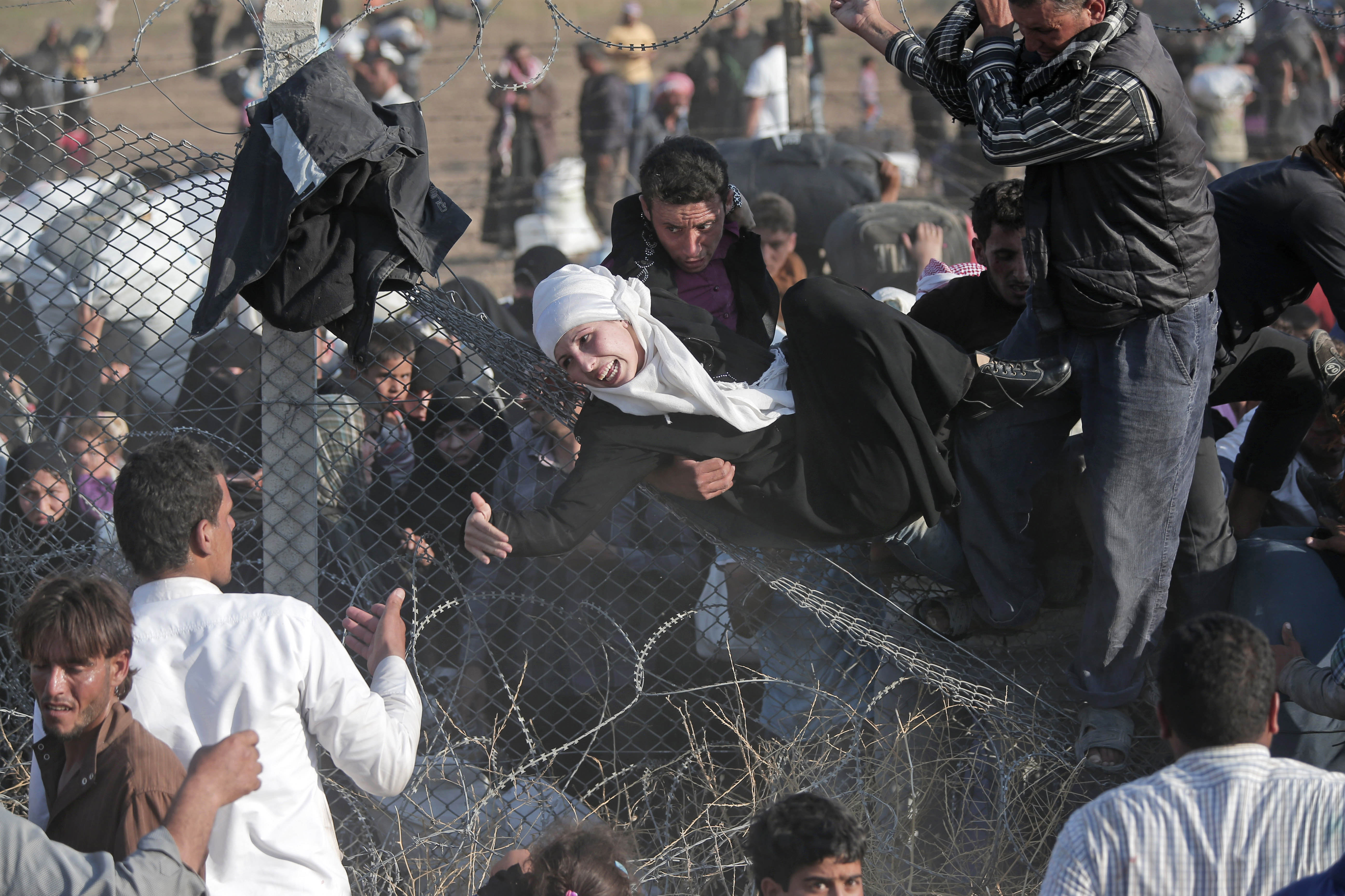 FILE - In this Sunday, June 14, 2015 file photo, Syrian refugees are helped into Turkey after breaking the border fence and crossing from Syria in Akcakale, Sanliurfa province, southeastern Turkey