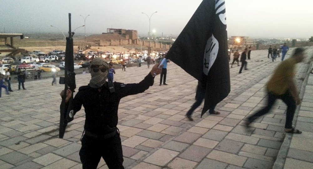A fighter of Daesh holds an ISIL flag and a weapon on a street in the city of Mosul, Iraq, in this June 23, 2014.