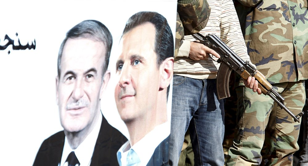 Syrian civilians who volunteered to join local Self Protection Units to protect their neighbourhoods alongside the Syrian army attend training near a picture of Syria's president Bashar al-Assad and his father late former president Hafez al-Assad, in Damascus countryside, Syria December 5, 2015