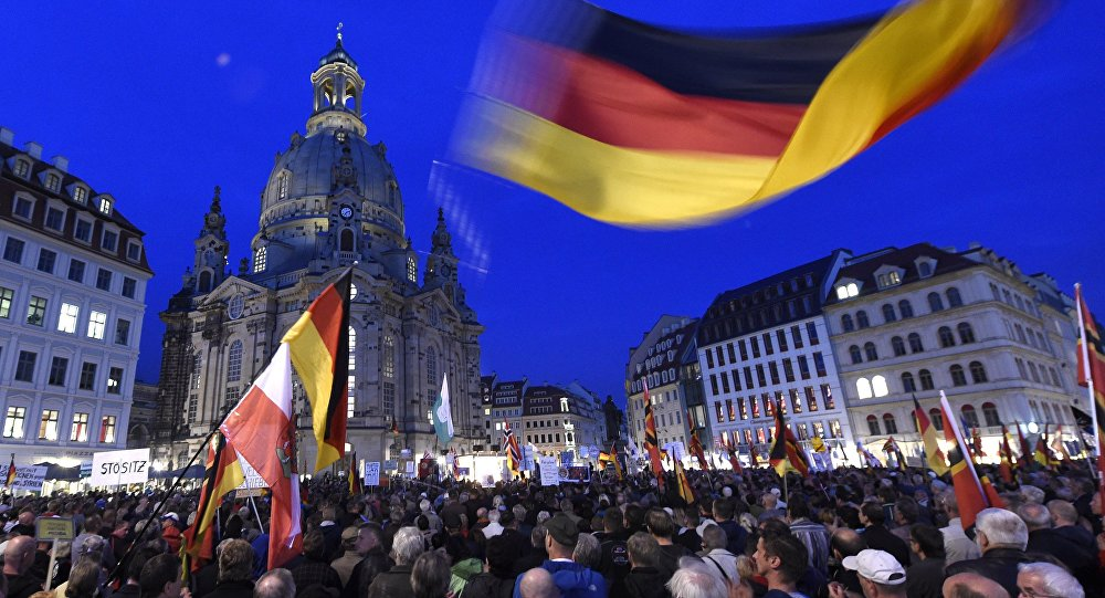 Protestors wave a German flag in front of the Church of Our Lady during a demonstration of PEGIDA (Patriotic Europeans against the Islamization of the West) in Dresden, eastern Germany
