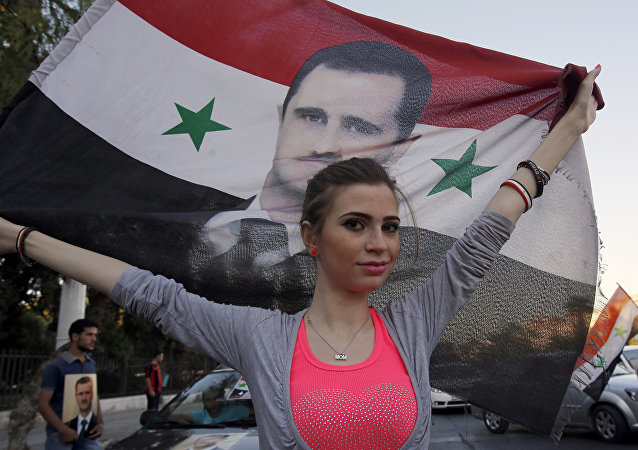 A Syrian girl holds her national flag bearing a portrait of Syria's President Bashar al-Assad