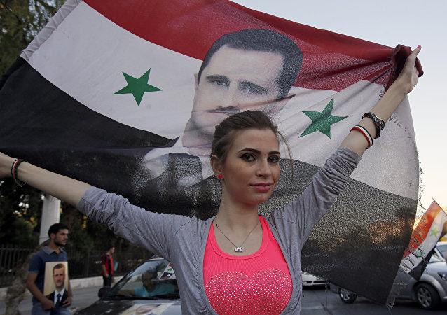 A Syrian girl holds her national flag bearing a portrait of Syria's President Bashar al-Assad