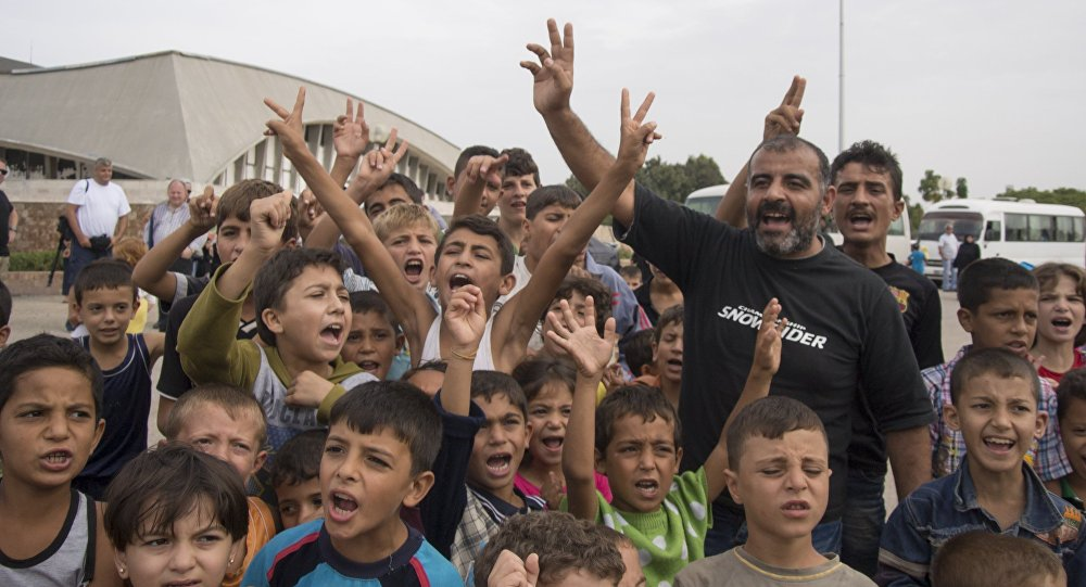 Refugees kids shout Thank you, Putin! while posing for journalists at a camp in Latakia, Syria, Friday, Oct. 23, 2015