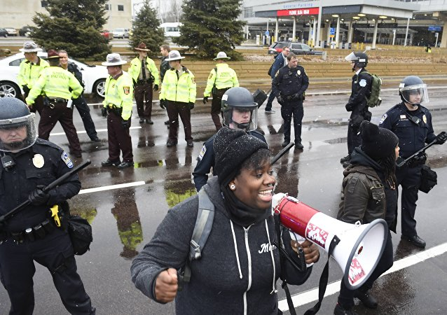 A protester named Oluchi of Minneapolis speaks to protesters after they shut down the main road to the Minneapolis St. Paul Airport following a short protest at the Mall of America in Bloomington, Minnesota December 23, 2015