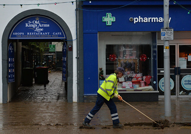 A worker clears silt and debris from a road in Cockermouth, northern England, on December 7, 2015 as the clean up starts following heavy flooding in the town caused by Storm Desmond