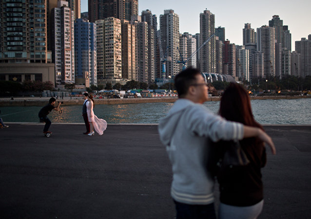 A couple (L) pose for their pre-wedding photographs on a public pier in Hong Kong on November 28, 2015.