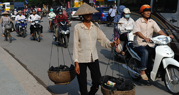 This picture taken on September 10, 2015 shows a migrant worker (C) carrying collected items for recycling walking along a road in downtown Hanoi