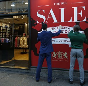 Two shop workers fix a sale sign onto their shop window on Regent Street in London, Thursday, Dec. 24, 2015. In Britain Dec 26, known as Boxing Day is the traditional start for shops to start their big sales of old stock