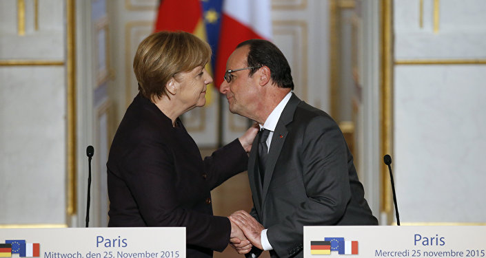 French president Francois Hollande, right, kisses German Chancellor Angela Merkel at the end of a joint press conference at the Elysee Palace, in Paris, Wednesday, Nov. 25, 2015