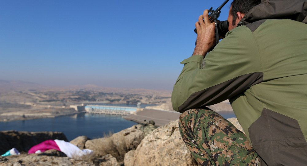 A fighter from the Democratic Forces of Syria takes an overwatch position at the top of Mount Annan overlooking the Tishrin dam, after they captured it on Saturday from Islamic State militants, south of Kobani, Syria December 27, 2015
