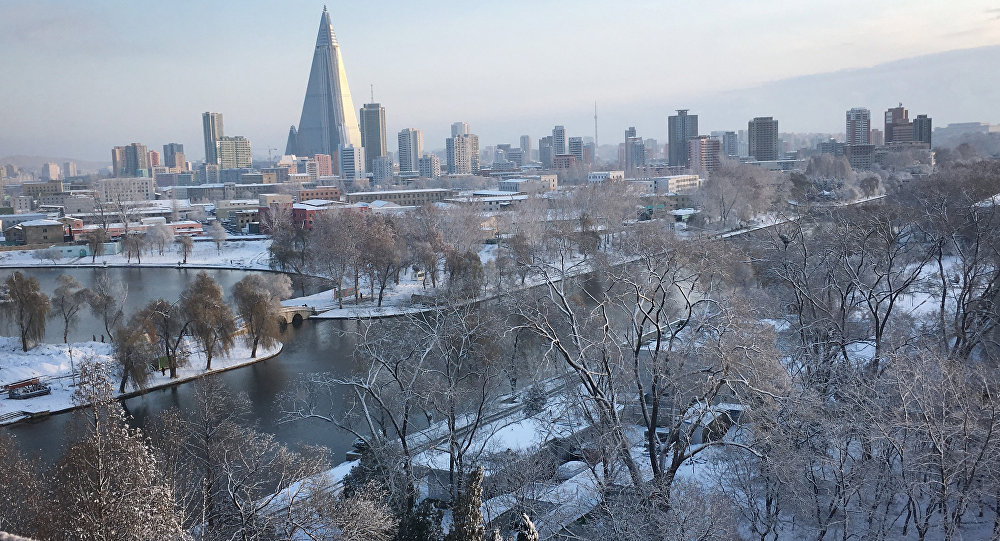 The 105-story pyramid-shaped Ryugyong Hotel towers over residential apartments and snow covered trees and fields on Thursday Dec. 3, 2015, in Pyongyang, North Korea where the winter season has started