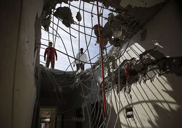 Men inspect a building damaged by a Saudi-led airstrike in Sanaa.