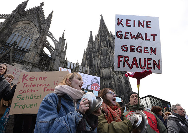 A man holds up a sign reading No violence against women as he takes part in a demonstration in front of the cathedral in Cologne, western Germany, on January 9, 2015 where sexual assaults in a crowd of migrants took place on New Year's Eve