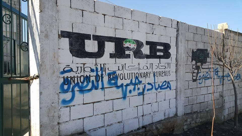 Photos released by social media accounts tied to Syrian rebels show a ransacked headquarters of an FSA coordinating center and radio station with Confiscated by al-Nusra Front spray-painted on the walls.