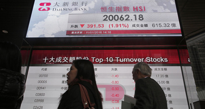 Passersby walk past an electronic board showing Hong Kong share index outside a local bank in Hong Kong, Monday, Jan. 11, 2016