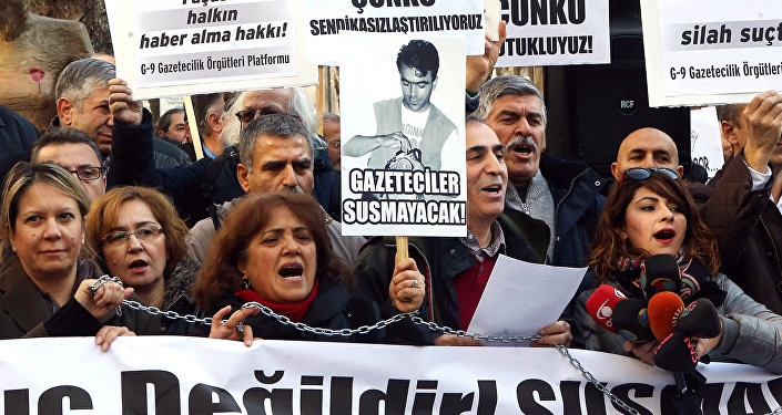 Turkish journalists hold banners and shout slogans during a demonstration in support of jailed journalists Can Dundar and Erdem Gul on January 10, 2016 in Ankara during the Active Journalists'Day