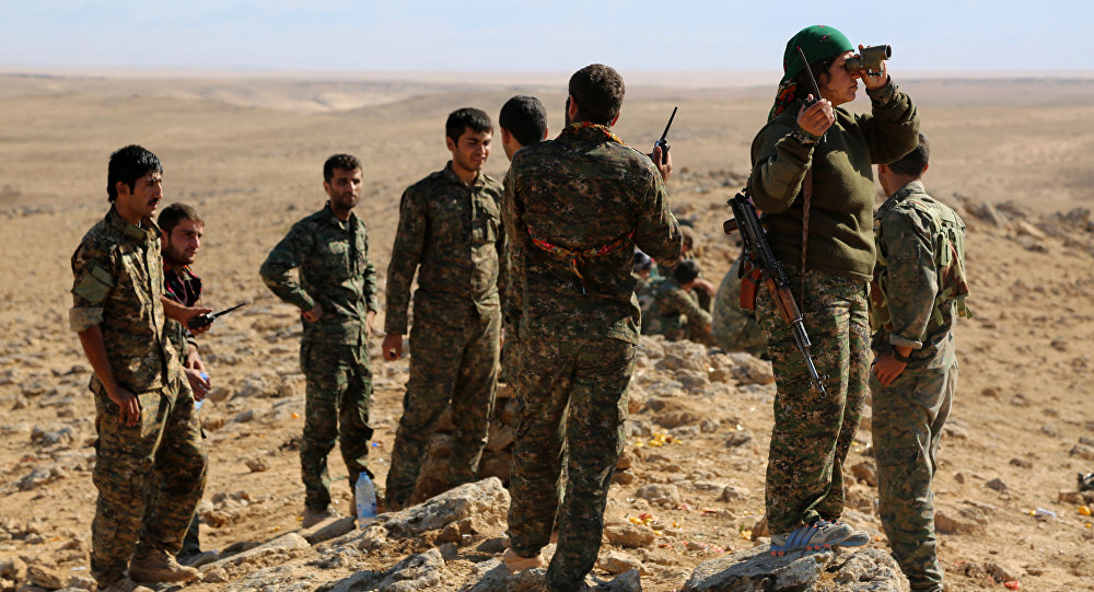 A group of coalition forces, which includes People's Protection Units (YPG) Women's Protection Units (YPJ), Sutoro militia, a pro-government Syriac Christian movement, and other forces, monitor the area in al-Hol in the Syrian Hasakeh province, some 650 kms northeast of Damascus, near the Iraqi border on November 2, 2015