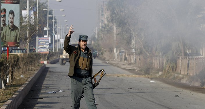 An Afghan policeman reacts as smoke billows during an attack near the Pakistani consulate in Jalalabad, Afghanistan January 13, 2016