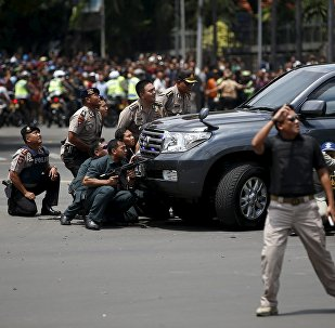 Police officers react near the site of a blast in Jakarta, Indonesia, January 14, 2016