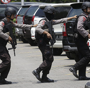 Police officers take their position near the site where an explosion went off in Jakarta, Indonesia Thursday, Jan. 14, 2016.