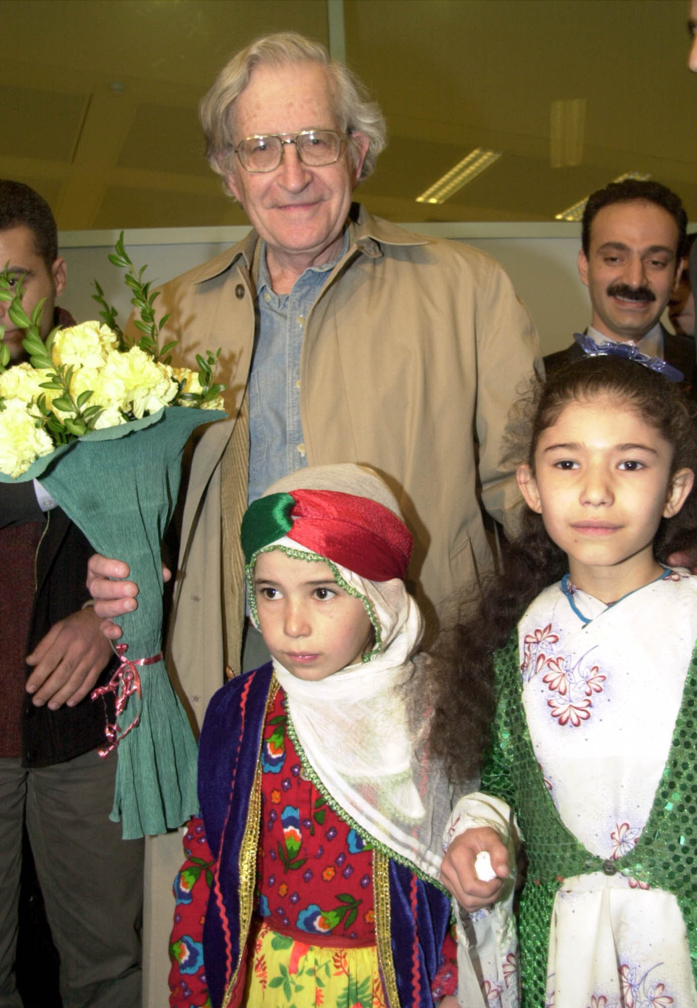 Noam Chomsky, the American linguist, is welcomed by children in traditional Kurdish outfits at Istanbul's Ataturk airport, Tuesday Feb. 12, 2002