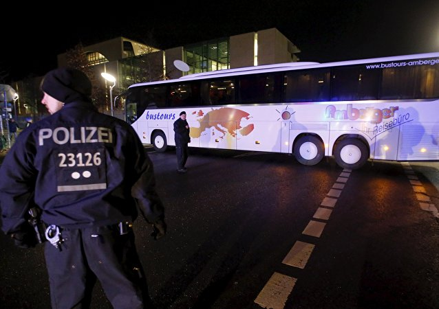 Police escort a bus carrying refugees from the Bavarian town of Landshut after it left the Chancellery building in Berlin, Germany, January 14, 2016