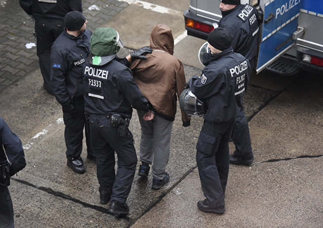Policeman march off a handcuffed refugee in Berlin