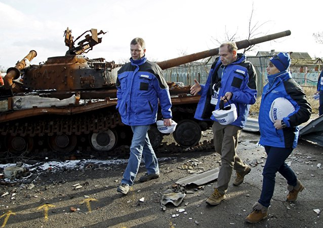 Deputy Chief of the Special Monitoring Mission of the Organization for Security and Cooperation in Europe (OSCE) to Ukraine Alexander Hug (L), with members of the mission, walks past a burnt tank as he inspects an area between self-proclaimed Donetsk People's Republic forces and Ukrainian government troops in the village of Kominternove north-east of the port city of Mariupol, Ukraine, January 15, 2016
